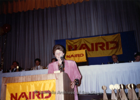 P168.002m.r.t National Association of Independent Record Distribution event: Karen Merry at podium next to a table of awards