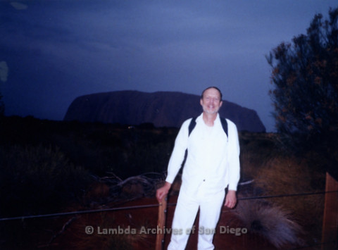 P338.074m.r.t Charles McKain wearing all white standing in front of Ayres Rock in Australia at night