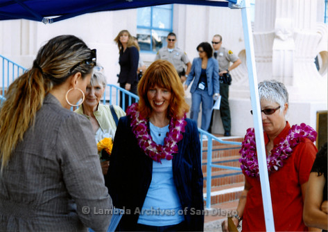 P249.008m.r.t First Same Sex Weddings in San Diego: Four women gathered outside under canopy, looking down and smiling