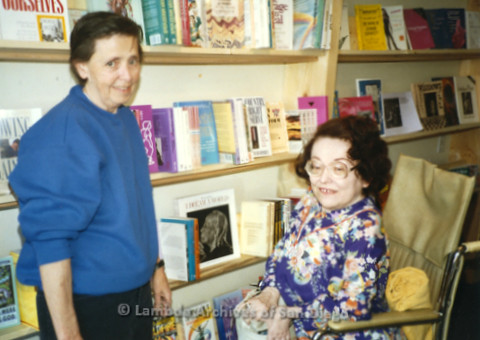 P169.004m.r.t Paradigm Women's Bookstore: Two women inside bookstore, one in wheelchair