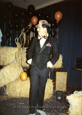 P099.069m.r.t Halloween: A man in a retro suit, standing in front of hay bales and balloons