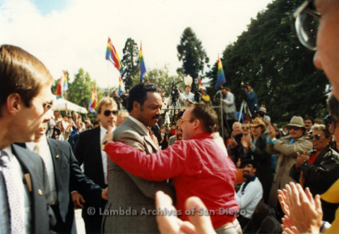 P019.130m.r.t March on Sacramento 1988 / Pre Parade gathering: Jesse Jackson in a crowd of people with a man giving him a hug