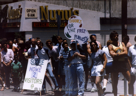 San Diego Lambda Pride Parade: The Parade Crowd holding Pro-LGBT signs across the street from Fundamentalist Christian Protesters. A Sign Reads, 'Thanks For The Free Publicity'.