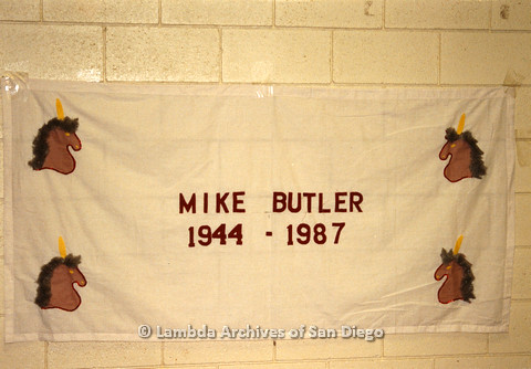 P019.030m.r.t AIDS Quilt at San Diego Golden Hall 1988: White quilt decorated with brown unicorns dedicated to Mike Butler