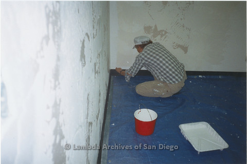 """P235.008m.r.t North County Center, San Diego: Person pasting border on wall with hat that reads: """"VISTA"""""""
