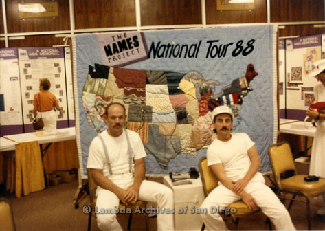 """P019.189m.r.t AIDS Quilt at San Diego Golden Hall 1988: Two men sitting in front of """"NAMES Project National Tour 88"""" quilt"""