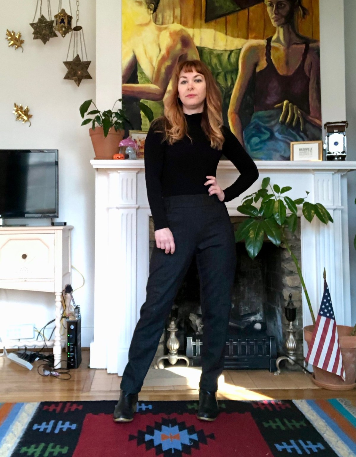 Lauren stands on a rug in front of a fireplace. She is wearing a black polo neck sweater and navy cigarette pants.