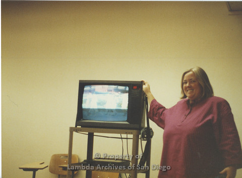 P024.042m.r.t LCCA: Woman posing infront of a television at SDSU.