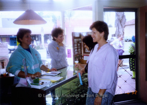 P167.004m.r.t Paradigm Women's Bookstore: Women gathered around counter of bookstore, talking