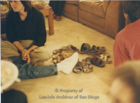 Alix Dobkin  Concert, 1985 in the home of Carol Cianfarani: Birkenstocks in a circle on the carpet; Night of the Living Birkenstocks. Karen Merry (top left) owner of Paradigm Feminist Bookstore.