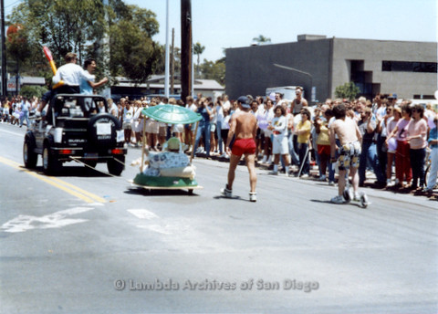 P018.029m.r.t San Diego Pride Parade 1988: Woman on a mini float being dragged by a truck