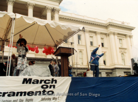 P019.153m.r.t March on Sacramento 1988 / Pre Parade gathering: Woman on stage speaking into a microphone while another woman raises her arms on side of stage