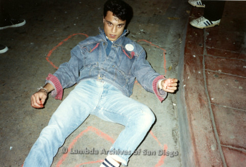 """P019.339m.r.t Los Angeles """"Die In"""" 1988:  Man laying on ground with chalk body outline, pin on jacket reads """"Being Alive"""""""