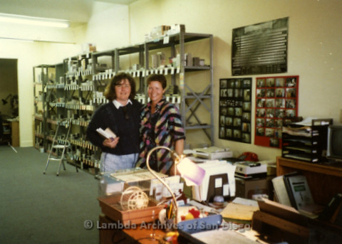 P169.079m.r.t Paradigm Women's Bookstore Grand Opening: Two women posing between desk and shelving