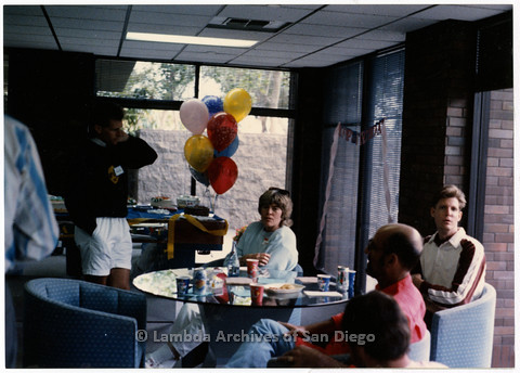 P201.029m.r.t San Diego AIDS Project 1989: Client mixer with men and a woman gathered around a table indoors