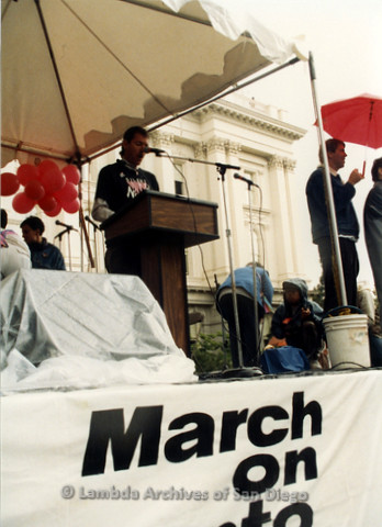 P019.157m.r.t March on Sacramento 1988 / Pre Parade gathering: Man speaking on stage