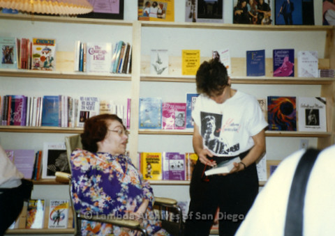 P169.047m.r.t Paradigm Women's Bookstore Grand Opening: Woman sitting in chair, woman standing with paperback book in bookstore
