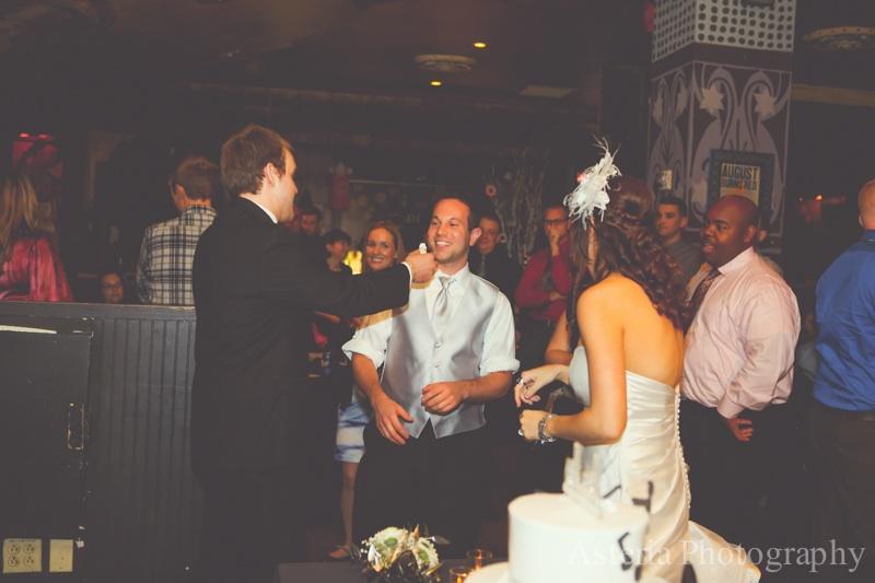 Bride and groom feeding cake to Groomsman
