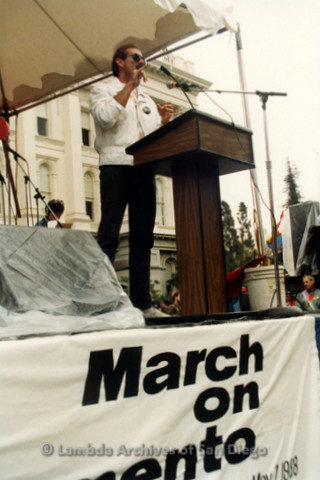 P019.139m.r.t March on Sacramento 1988 / Pre Parade gathering: Man speaking on stage in front of City Hall