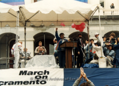 P019.154m.r.t March on Sacramento 1988 / Pre Parade gathering: Woman on stage with her fist in the air