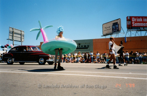 P018.176m.r.t San Diego Pride Parade 1999: Man marching in an island innertube