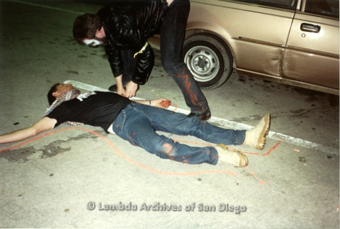 """P019.368m.r.t Los Angeles """"Die In"""" 1988: Man laying on ground while another man draws red chalk outline around him."""