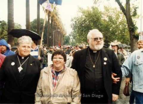 P019.181m.r.t March on Sacramento 1988 / Parade gathering: David Farrell (right) and two women (one in clerical collar) standing in crowd