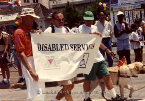 "P240.070m.r.t San Diego Pride Parade: People walking with banner for ""The Center Disabled Services."""