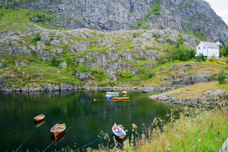 A fjord in the Lofoten Islands with a rocky mountain wall behind, a white house and rowing boats on the water
