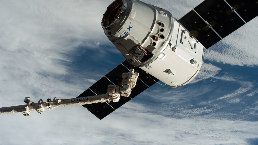 The Canadarm2 robotic arm reaches out to grapple the SpaceX Dragon