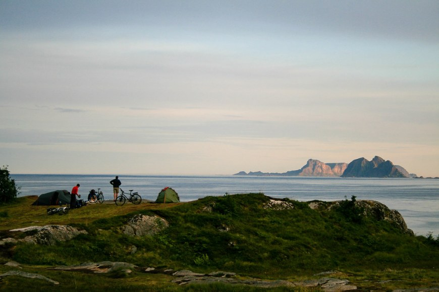 View of two people on a cliff, looking towards the sea, having their bikes and tents set up next to