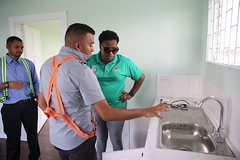 Minister within the Ministry of Communities with responsibility for Housing, Hon. Annette Ferguson inspects inside one of the houses.