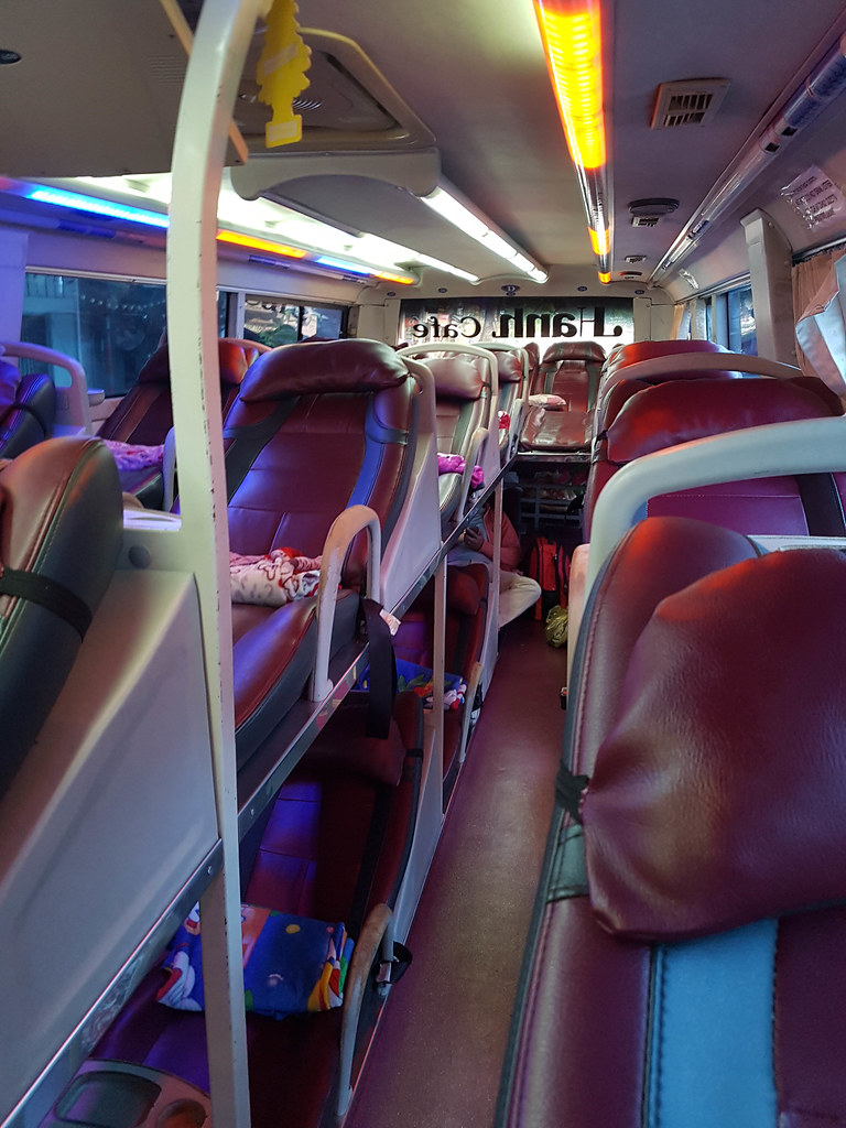 The interior of the sleeper bus from Ho Chi Minh City to Mui Ne: red reclaining chairs on two rows up and 3 rows horizontal