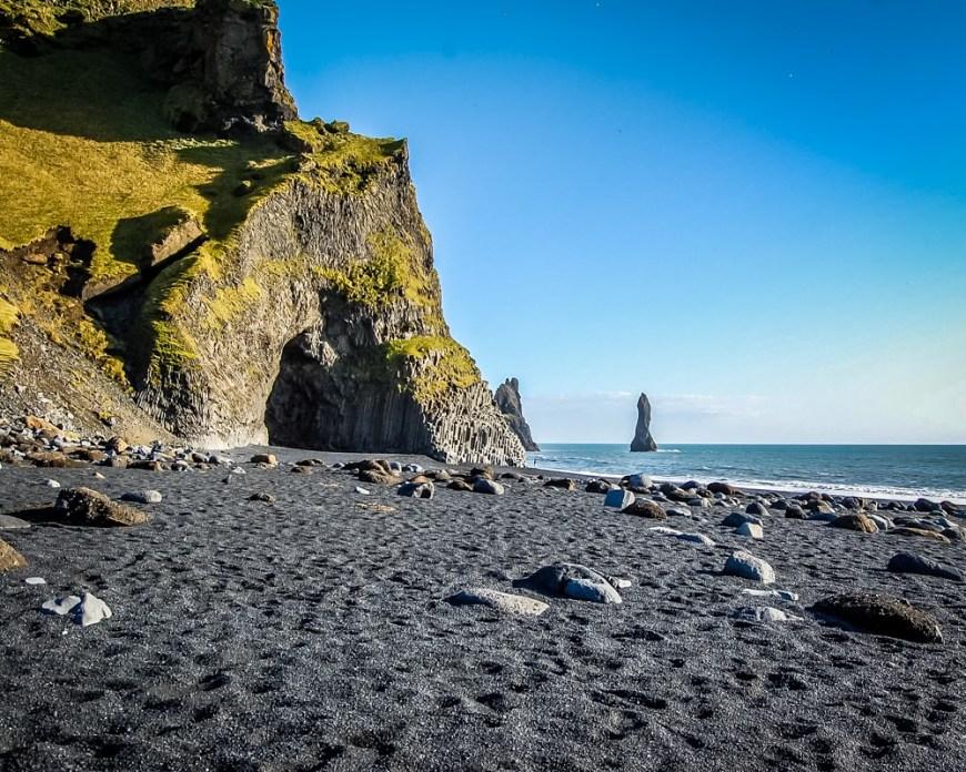 A beach with black sand on a very sunny day, with a blue sky