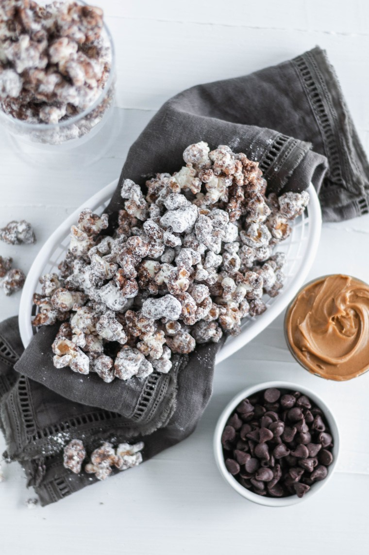 Update your game day snacking with this Puppy Chow Popcorn. Peanut butter and chocolate coated popcorn tossed in powdered sugar. Addiction ahead.