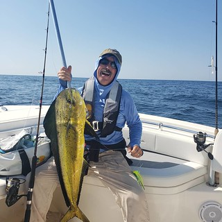 Photo of man holding a large Mahi Mahi