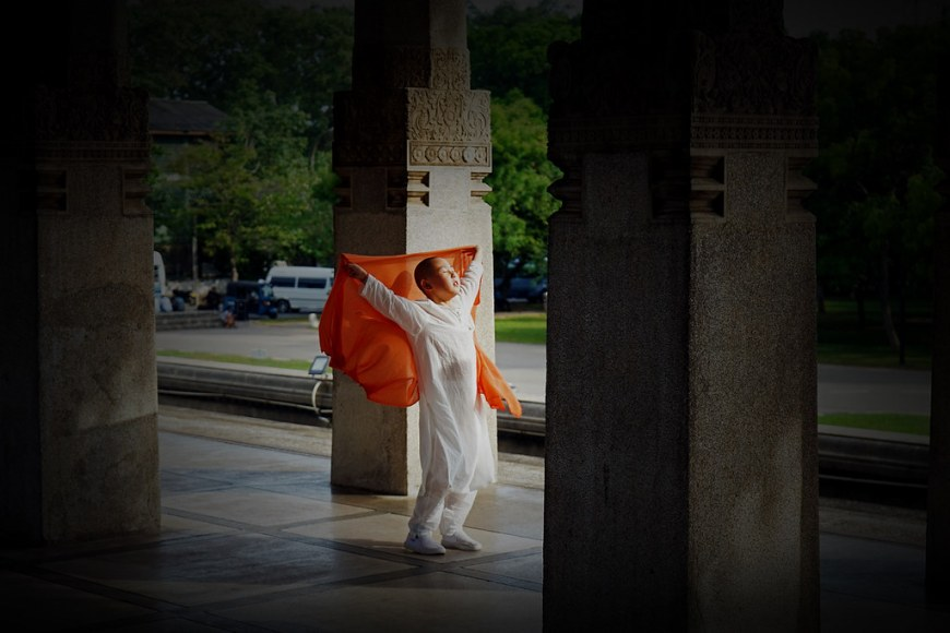 A child dressed in a white shirt and white pants is holding an orange scarf above it's hand. He is standing in the middle of the photo. Around him, there are dark columns.
