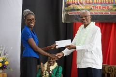 President David Granger hands over the cheque to Headteacher of New Amsterdam Multilateral School, Vanessa Jacobs.