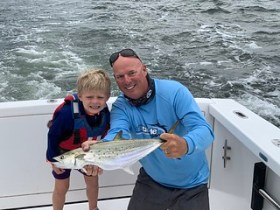 Photo of boy and man holding a Spanish mackerel