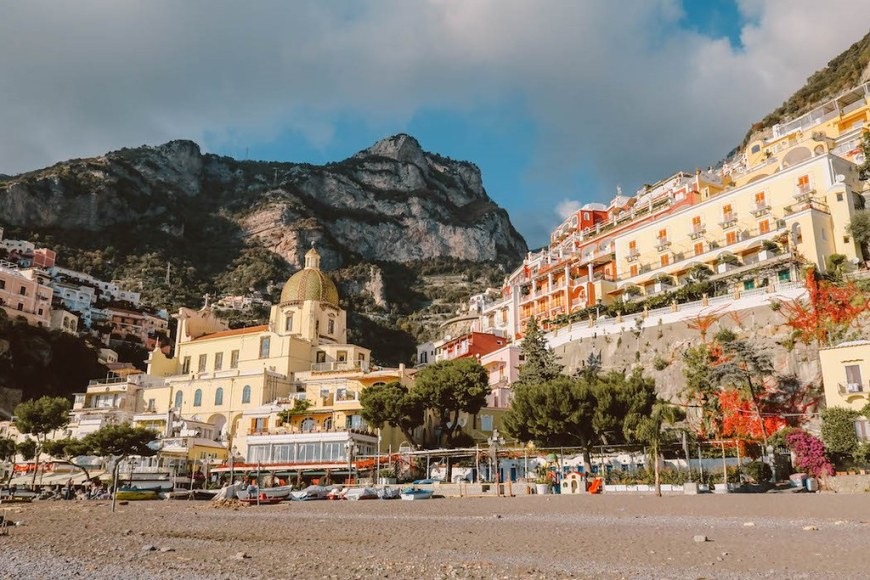 The beach in Positano, with a yellow church on the left and a tall cliff behind it
