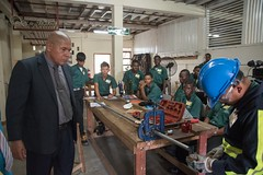 Minister of Social Cohesion, Dr. George Norton pays keen attention as one of the trainees demonstrates her skill.