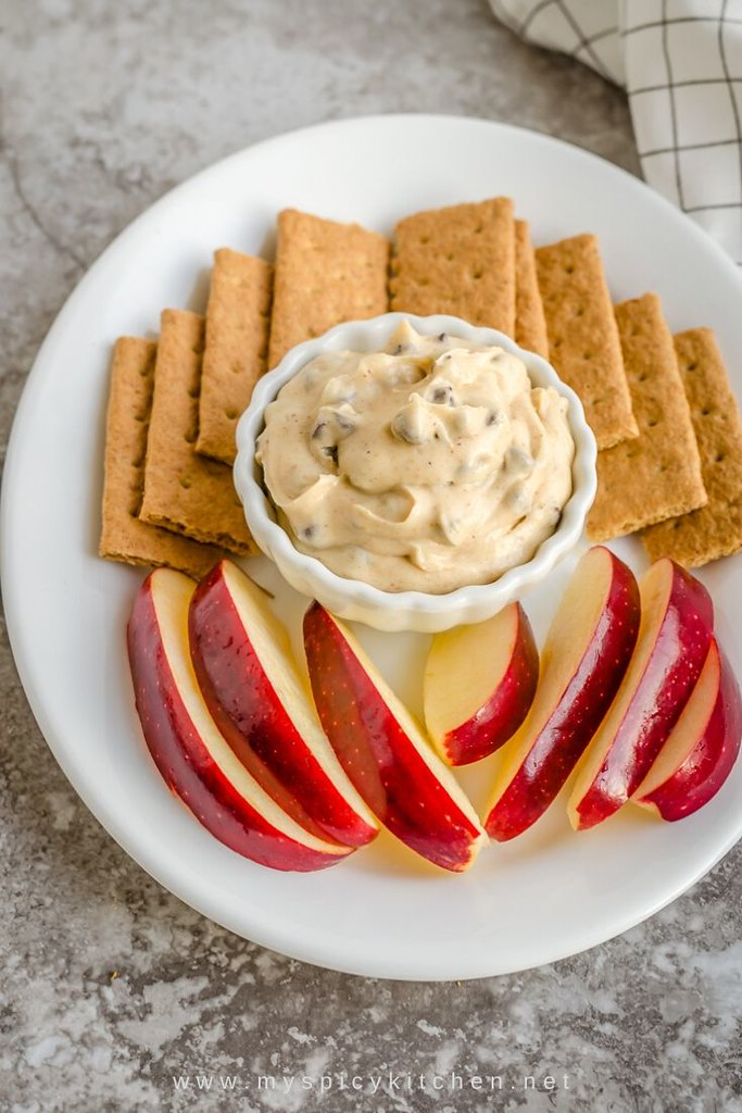 Platter of graham crackers and apples with a bowl of almond choco chip cookie dough dip