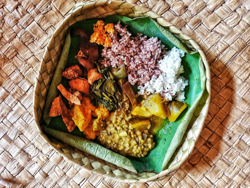 A bamboo bowl filled with colorful food: yellow dhal, orange pumpkin curry, yellow potatoes, white rice, redish wild rice, brigh orange sambol, green steamed salad. They all stay on a green banana leaf inside the bowl.