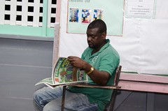 A resident reading Berbice Bulletin, a DPI publication.
