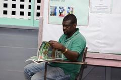 A resident reading Berbice Bulletin, a DPI publication.