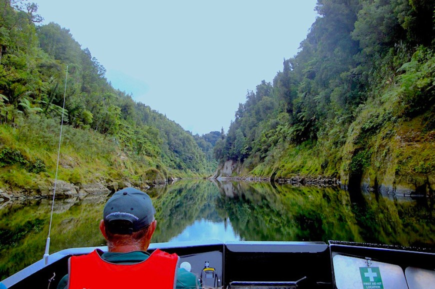 A man driving a boat on a very still river in which the trees on both sides reflect into