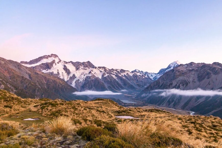 A sunset photo of Mount Cook, with warm color tones. Clouds are passing by below the cliffs, above the valley