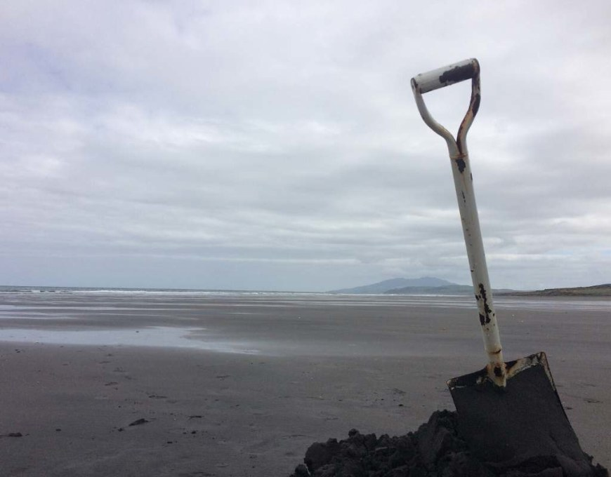 A beach at low tide, with a shovel in the foreground of the photo. The sand is black