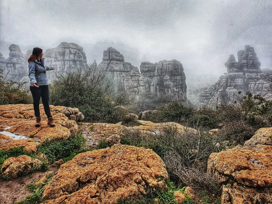 Joanna standing on some brown rocks, in the left of the photo, pointing towards the cliffs behind her. They are surrounded by fog and appear almost as if they were black and white