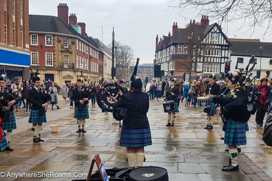 A group of bag pipe singers are gathered around in a circle, performing at their instruments. They are all wearing blue kilts, white socks and black jackets. People are gathered around them, watching.